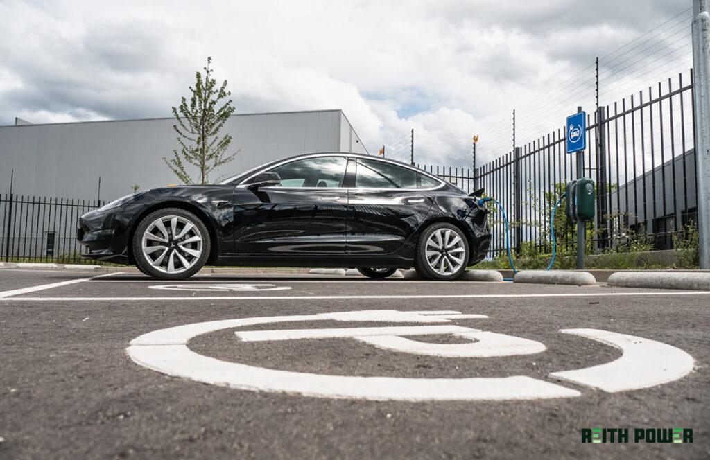 Tesla aan een laadpaal op een laadplein